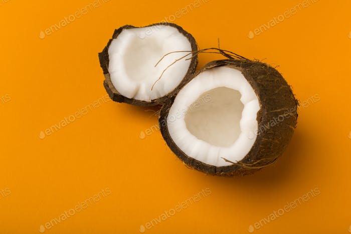 Broken coconut on bright yellow background