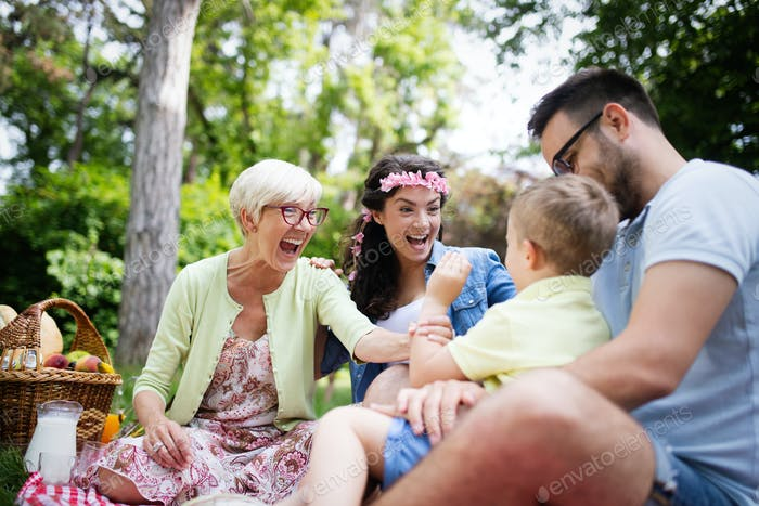 Happy family playing and enjoying picnic with children outside
