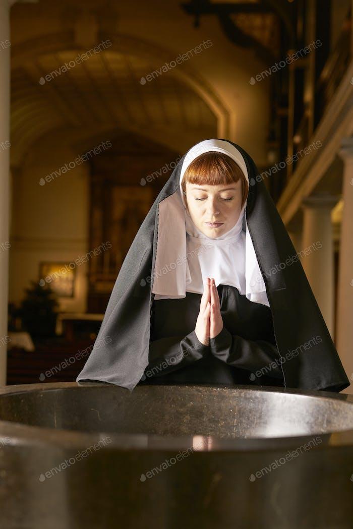 nun in church looking down praying at font