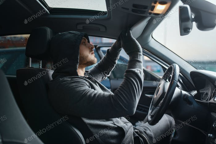 Car robber searches the interior, dangerous hobby