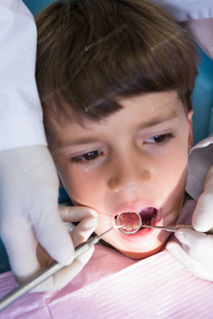 Boy looking away while receiving dental treatment at clinic