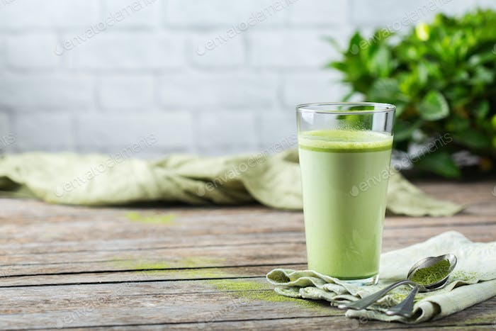 Glass of matcha green tea latte on a wooden table