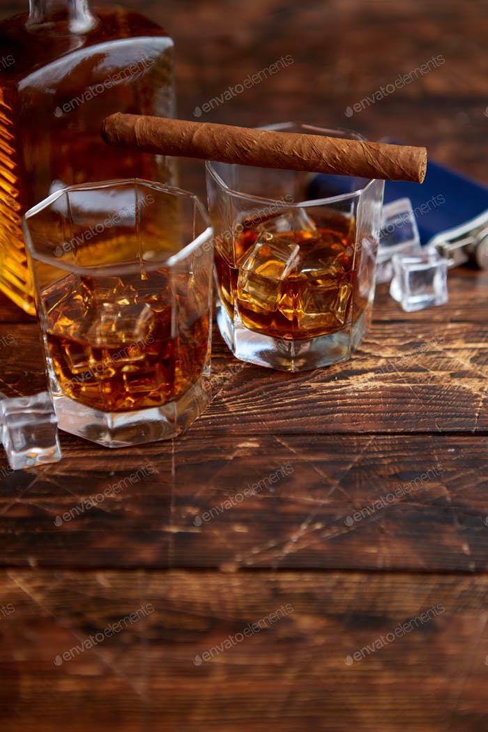 Bottle of whiskey with two glasses and cuban cigar placed on rustic wooden table