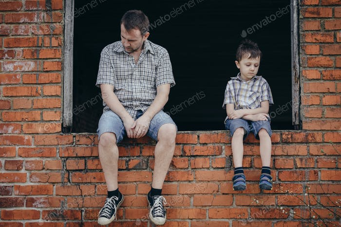 Portrait of sad little boy and father.