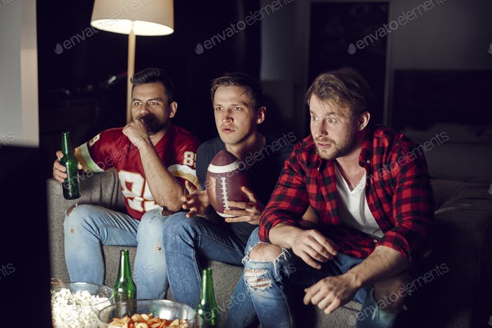 Football fans watching match with beers and snacks