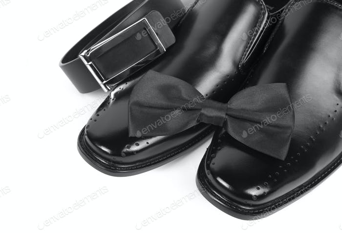 Close up of black male shoes, bow tie and belt