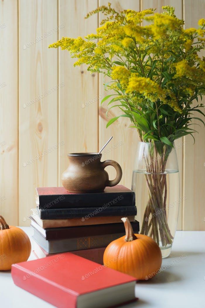 Herbst Stillleben mit Bücher, Kürbisse, Tasse, solidago Strauß