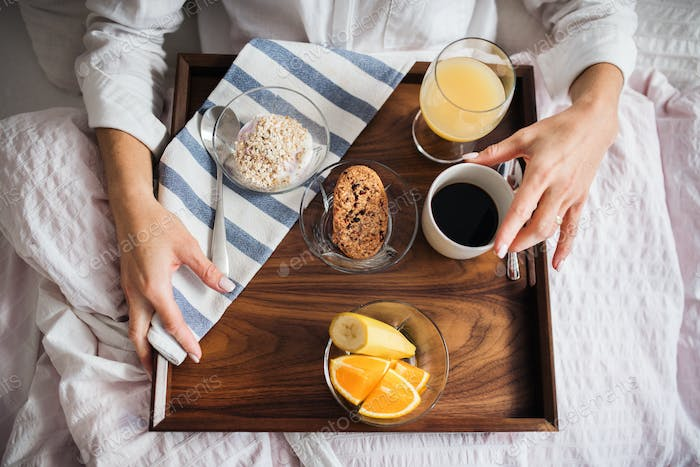 A midsection of woman with breakfast in bed in the morning. A top view.