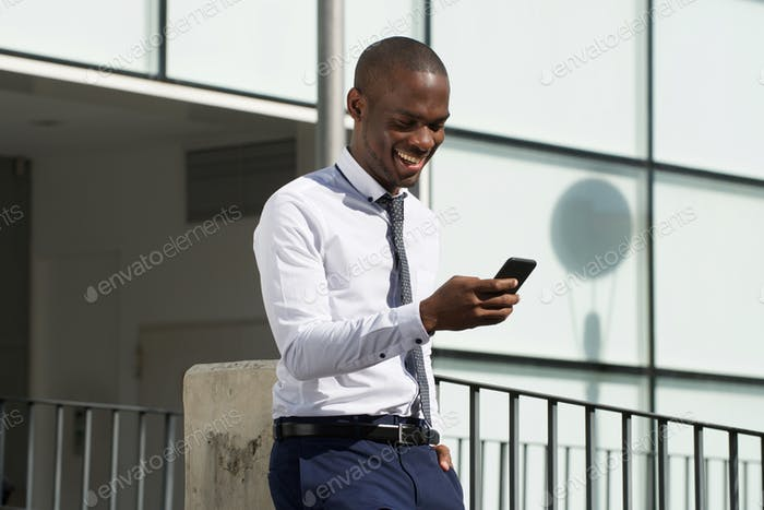 african american businessman looking at mobile phone in the city