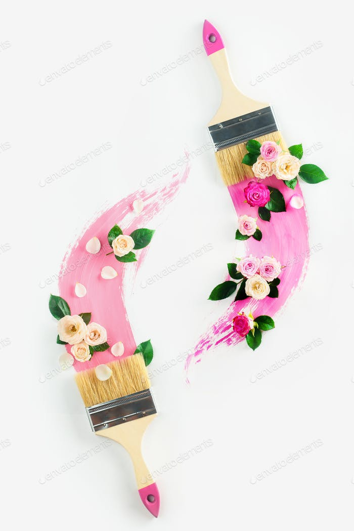 Home decoration concept with paintbrushes and flower arrangements, roses and petals, on a white