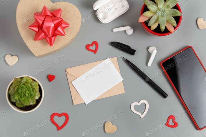 Placeit - Valentines gift and black card near hearts, succulent plants, earphones and smartphone