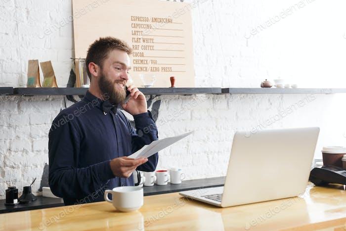 Пенсивный бармен, работающий на ноутбуке у барной стойки