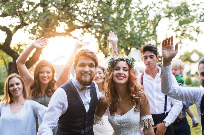 Невеста, жених, гости позируют за фото на свадебном приеме снаружи во дворе.