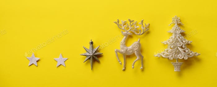 Silver Christmas decoration - deer, fir-tree, stars, cone on yellow background with copy space