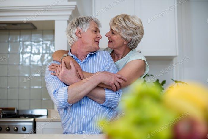 Seniorenpaar umarmen einander in Küche