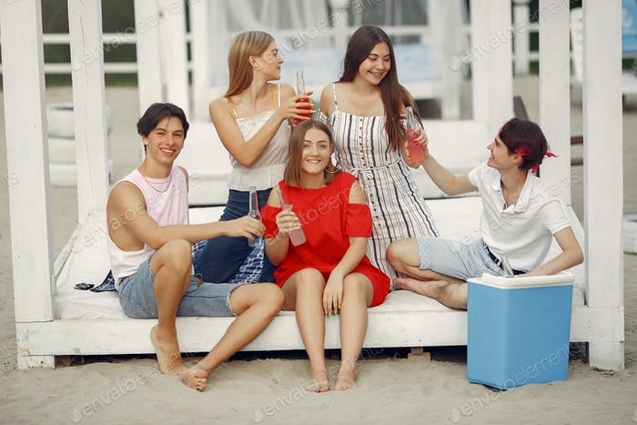 Friends have fun on a beach with drinks