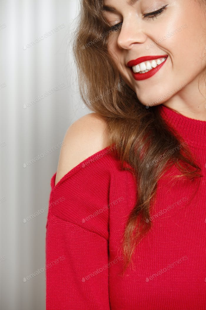 Stylish charming girl with red lipstick dressed in a red sweater poses poses against a white wall in
