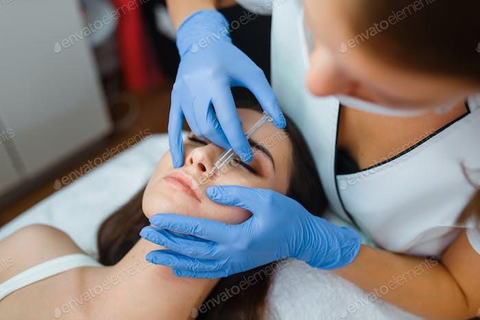 Kosmetikerin gibt Gesicht Botox-Injektionen an Patienten