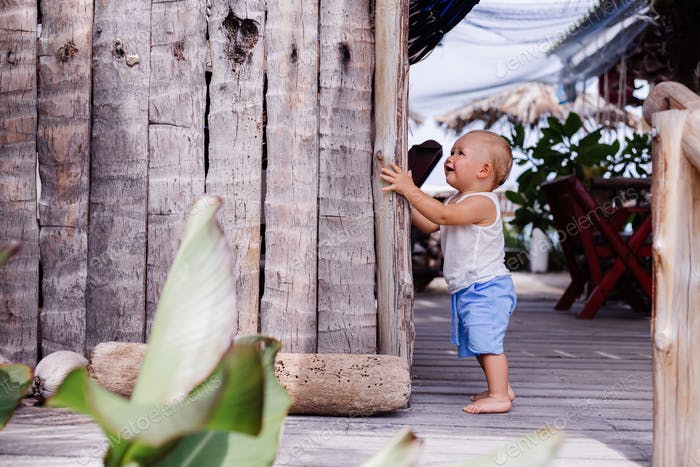Outdoor portrait of happy nine months old kid in blue short and white shirt