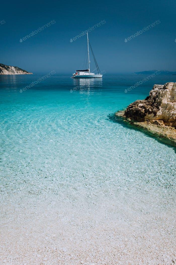 Beautiful azure blue lagoon with sailing catamaran yacht boat at anchor. Pure white pebble beach