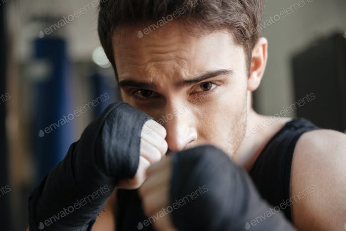 Close up  view of serious boxer doing exercise in gym