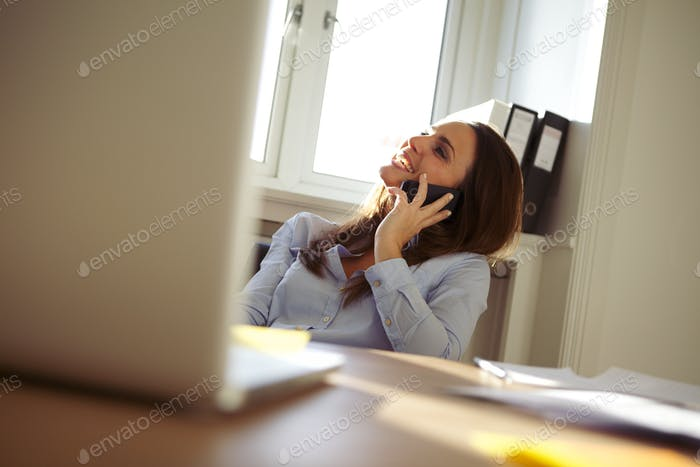 Beautiful businesswoman in home office talking on mobile phone