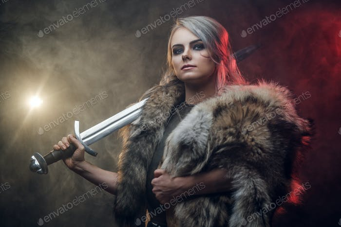 Portrait of a beautiful warrior woman holding a sword wearing steel cuirass and fur