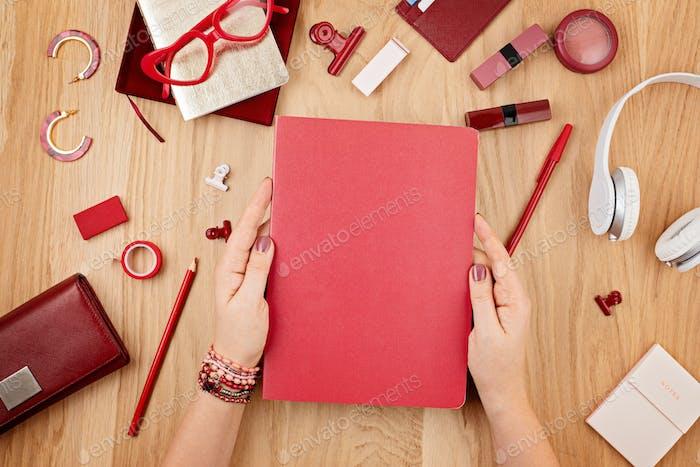 Woman's hands holding personal journal mockup for design over wooden desktop background, flat