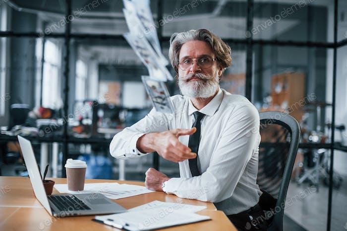 Tirando dinero. Hombre de negocios maduro con el pelo gris y la barba en ropa formal está en la oficina