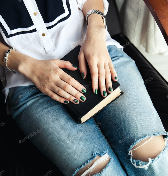 Stylish girl in torn jeans reading a book with a beautiful green manicure