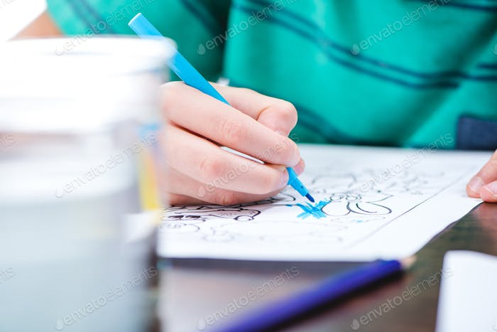 Close-up partial view of child drawing picture in coloring book
