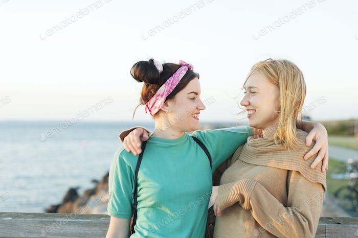 Happy female friends with arms around against beach