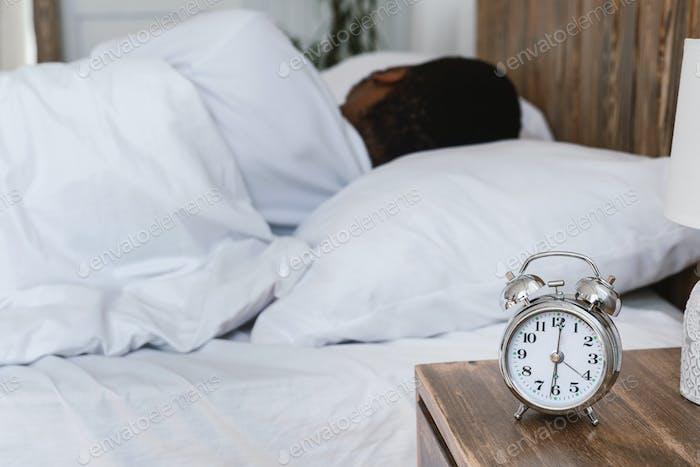 Overslept Black Man Sleeping Through Alarm-Clock Lying In Bed Indoor