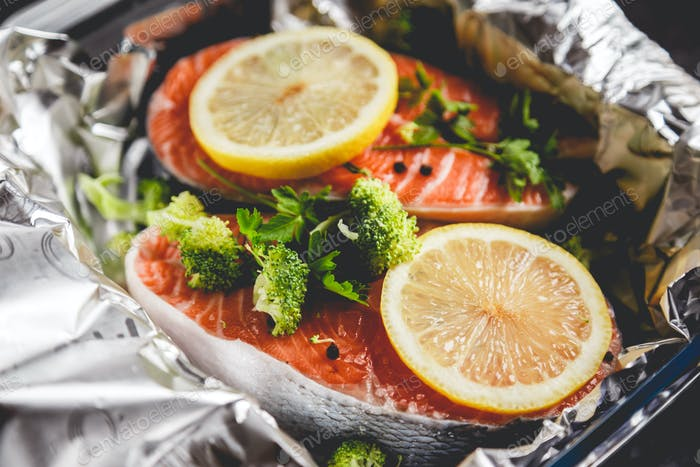 Raw sockeye salmon steaks on foil before baking in oven