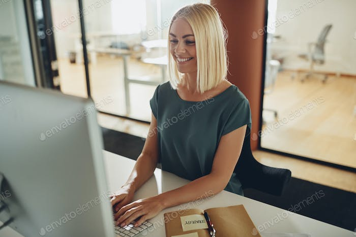 Smiling businesswoman working at her computer in the afternoon