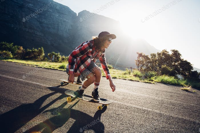Man longboarding outdoors on countryside road
