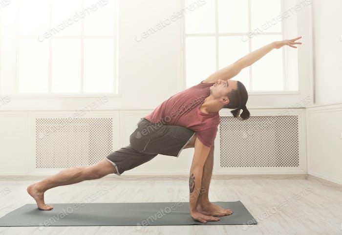 Mann Stretching Hände und Beine im Fitnessstudio