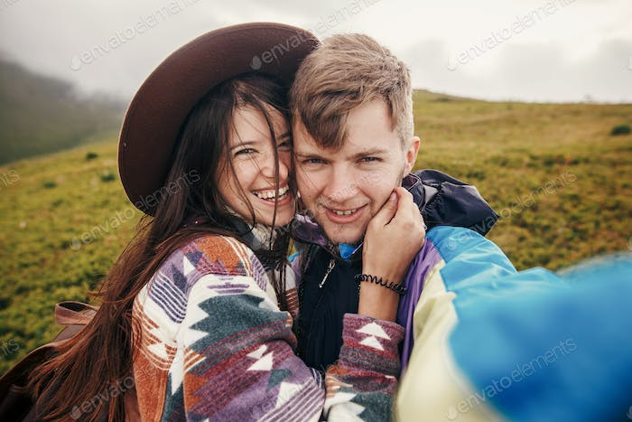 happy hipster couple making selfie on top of sunny mountains