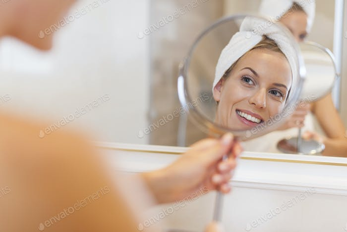 Beautiful woman looking herself reflection in small mirror