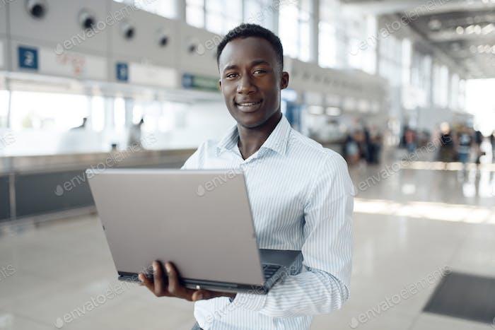Geschäftsmann arbeitet am Laptop im Auto-Showroom