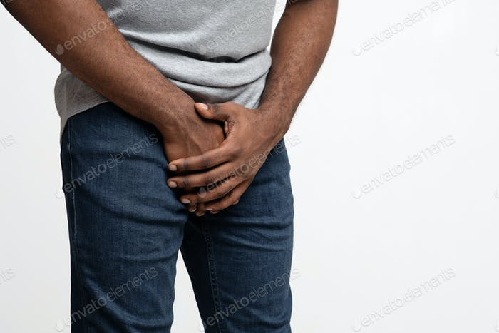 Cropped of black guy holding his groin