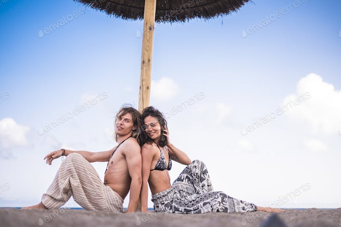 happy couple in holiday summer vacation sitting together at the beach