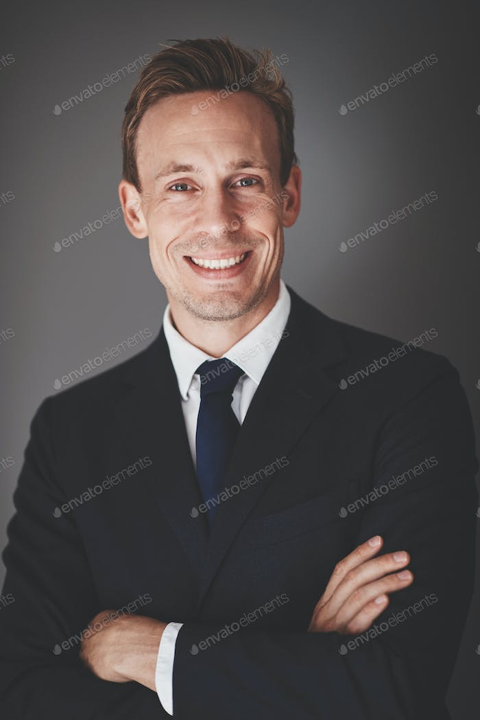 Young businessman smiling confidently while standing against a gray background
