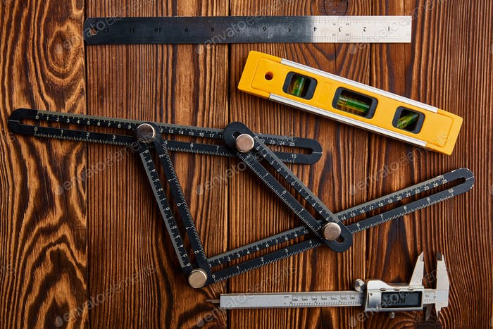 Level, ruler and caliper, wooden background