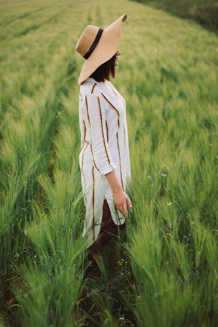 Stylish girl enjoying peaceful evening in countryside