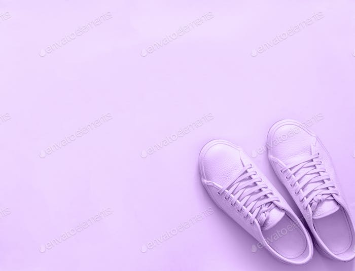 violet sneakers on violet background, copy space