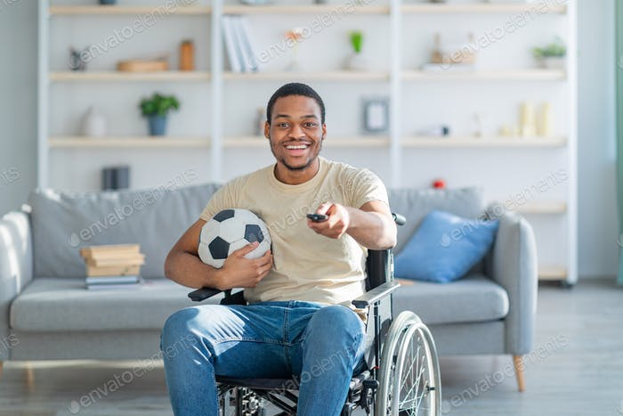 Cheerful impaired black guy in wheelchair watching football game on TV at home