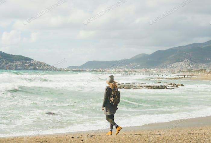 Young woman traveler looking at stormy Mediterranean sea, Alanya, Turkey
