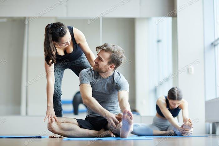 Yoga teacher adjusting pose of young man