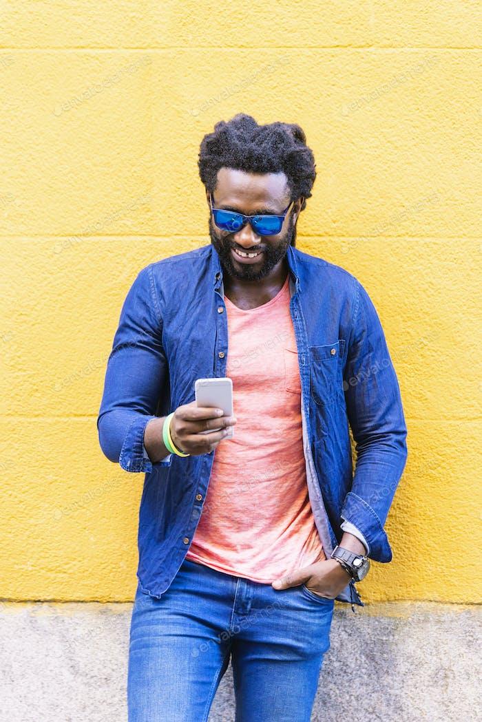 Jovem africano usando celular na rua.